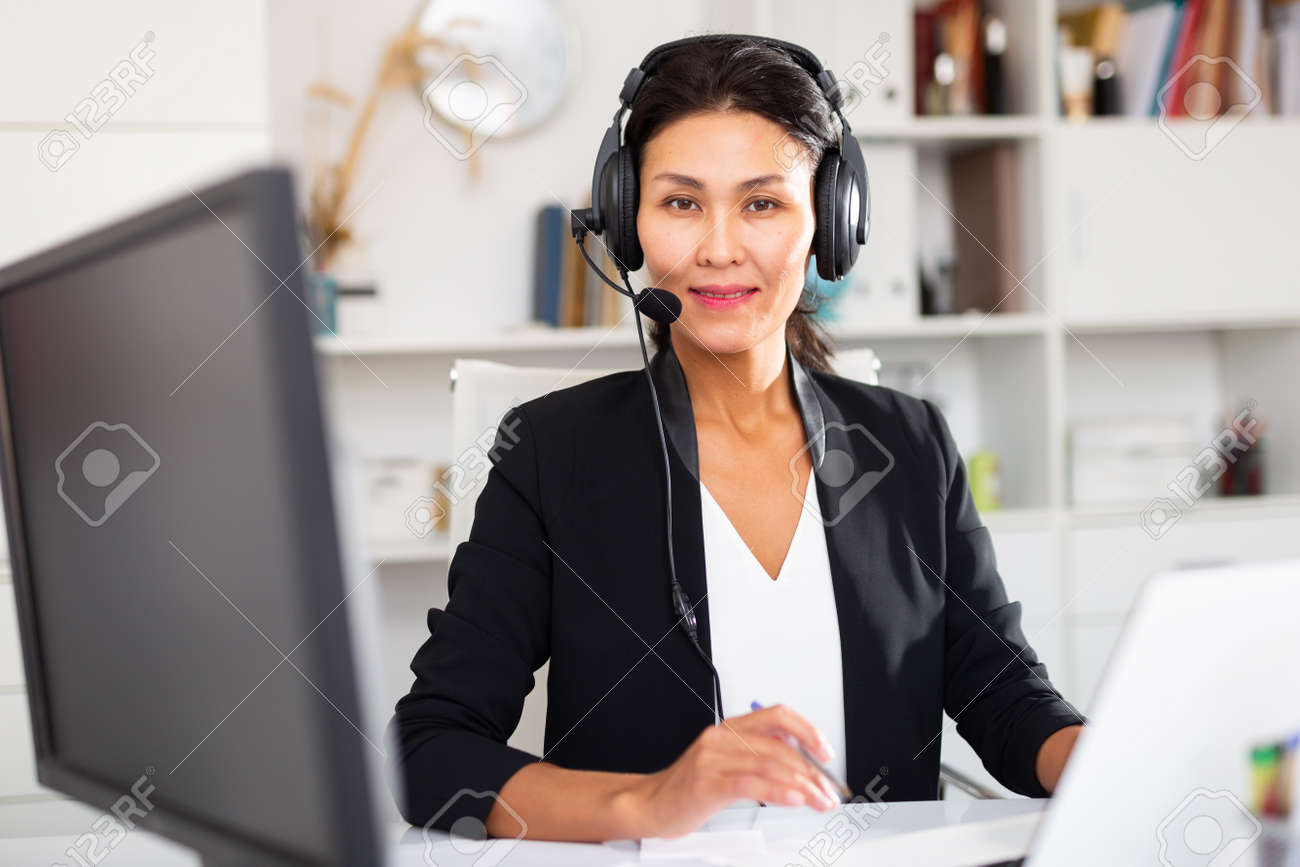 Office worker woman is working at a computer and talking by headset with client in office - 158666491