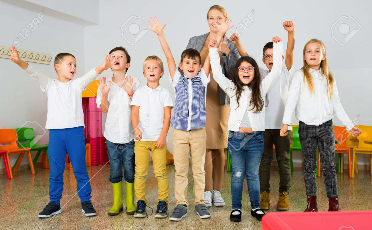 Portrait of cheerful female teacher with her happy schoolkids in classrom - 159106949