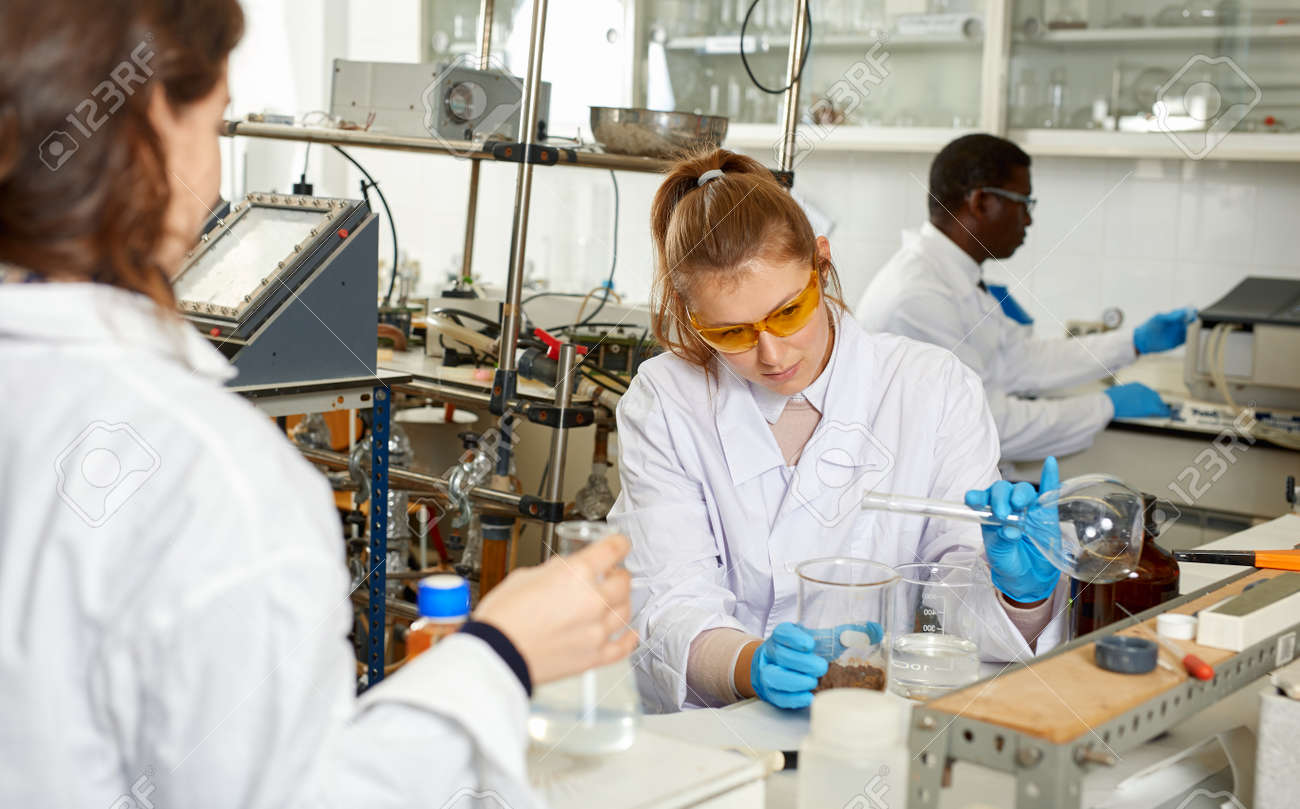 Woman lab technicians in glasses working with reagents and test tubes - 160083271