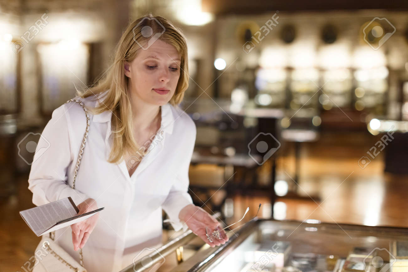 Woman visitor looking to art objects under glass with guide book in museum - 160422319