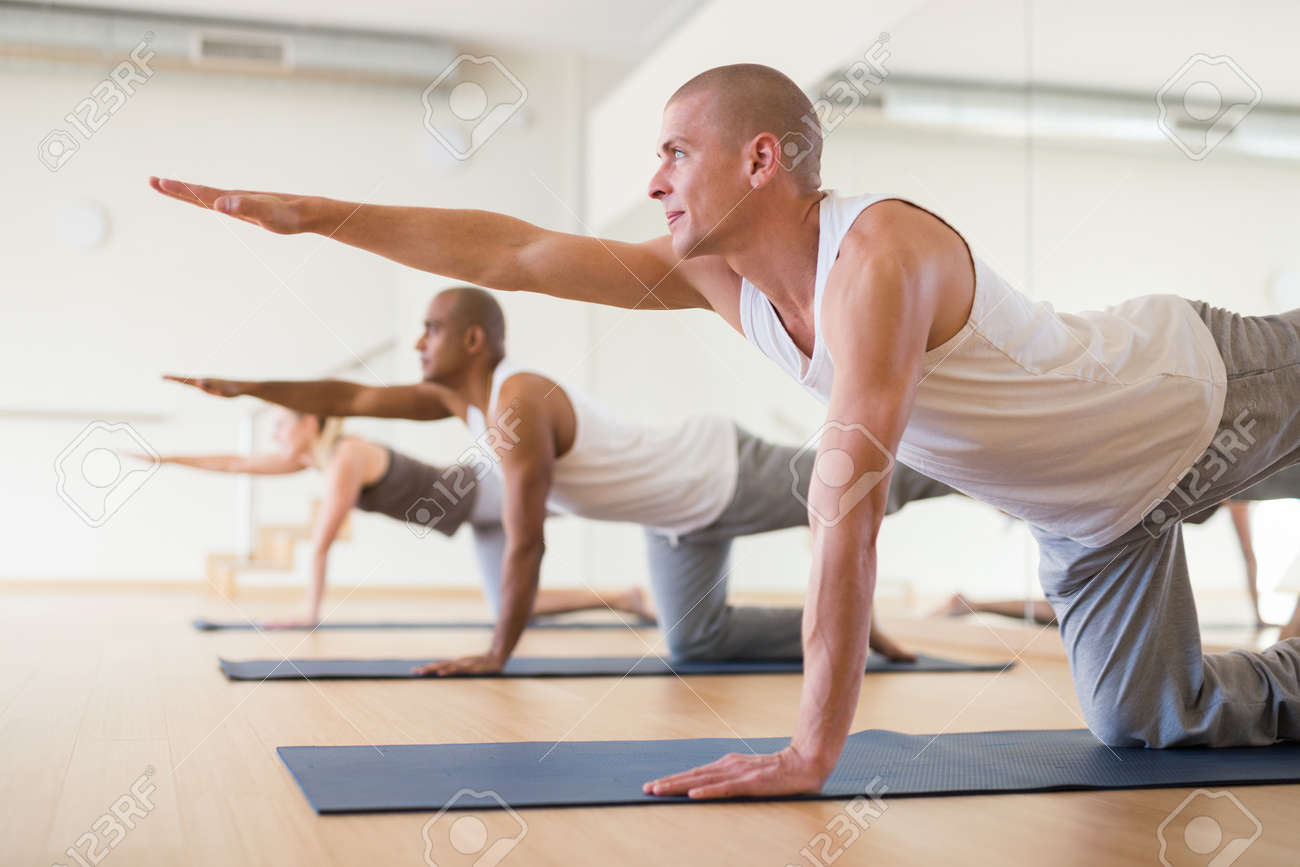 Man practicing Dandayamna Bharmanasana during group yoga training - 166650256