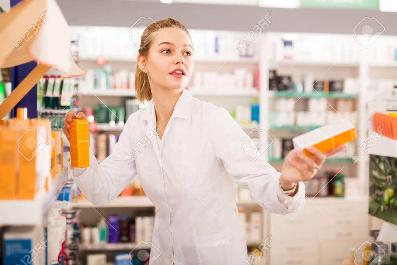 Pharmacist offering medicine in pharmacy - 167528675