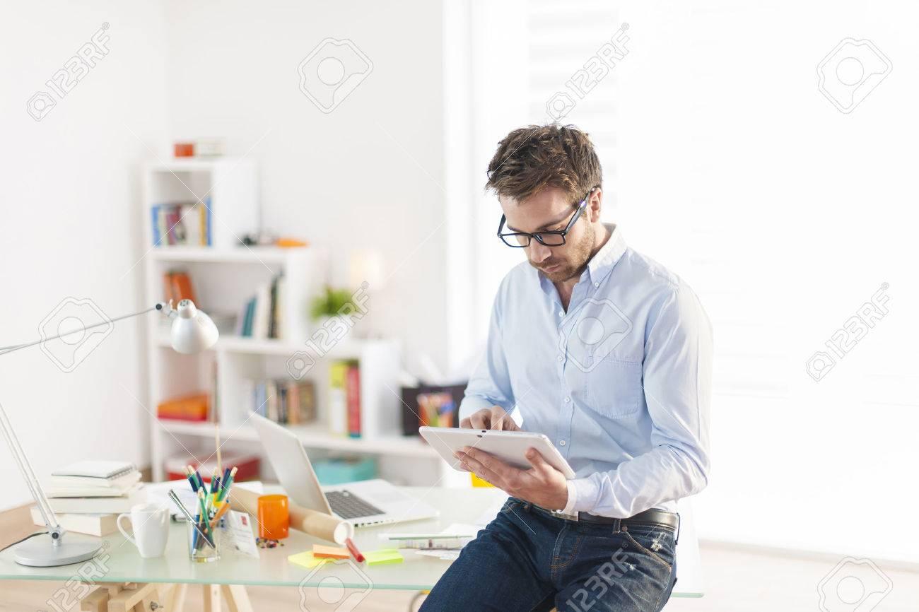 Banque d images - Jeune homme utilisant une tablette numérique au bureau 8e95f778bc4