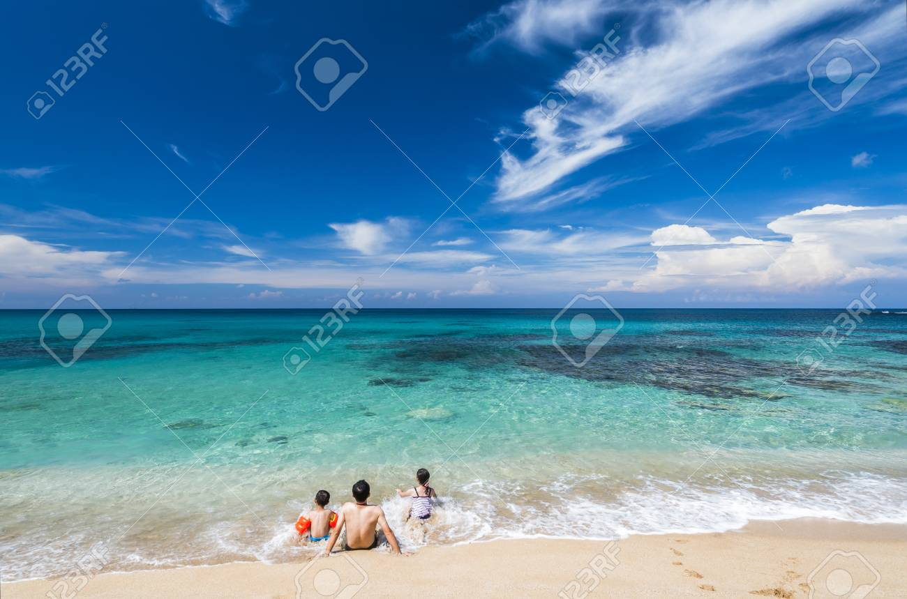 family with kids sitting on beach - 93918796
