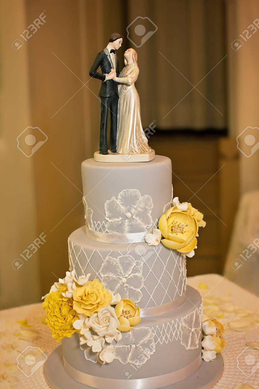 A Grey And White Themed Wedding Cake With Yellow Flowers And..