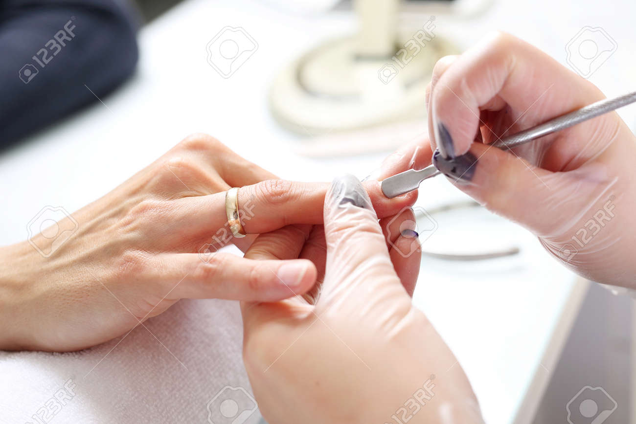 Hands beautifying treatment, woman in a beauty salon on a manicure procedure. - 137173401