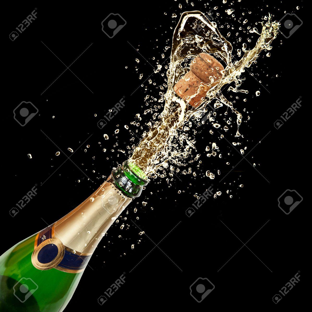 Celebration theme with splashing champagne, isolated on black background Stock Photo - 16725449