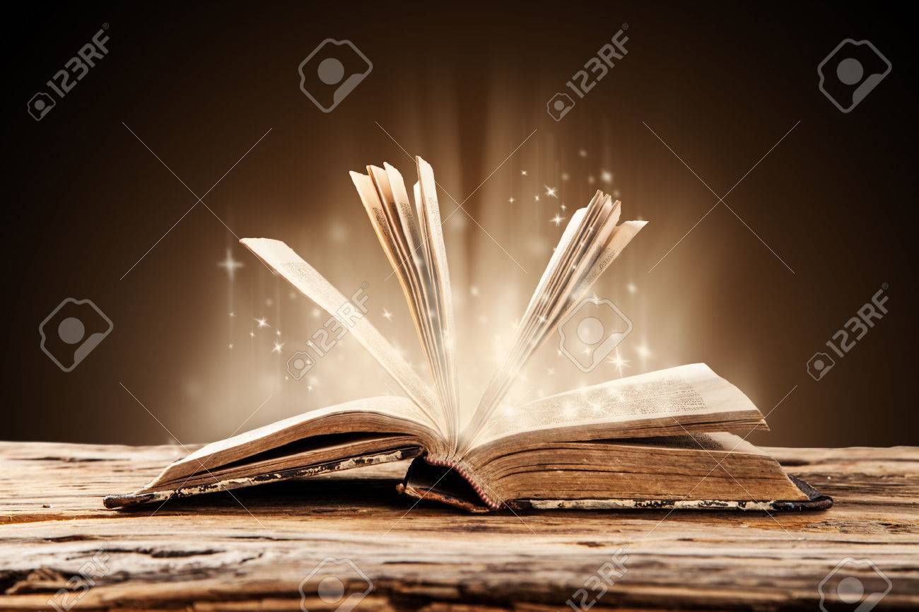 Old book on wooden planks with blur shimmer background - 32176134