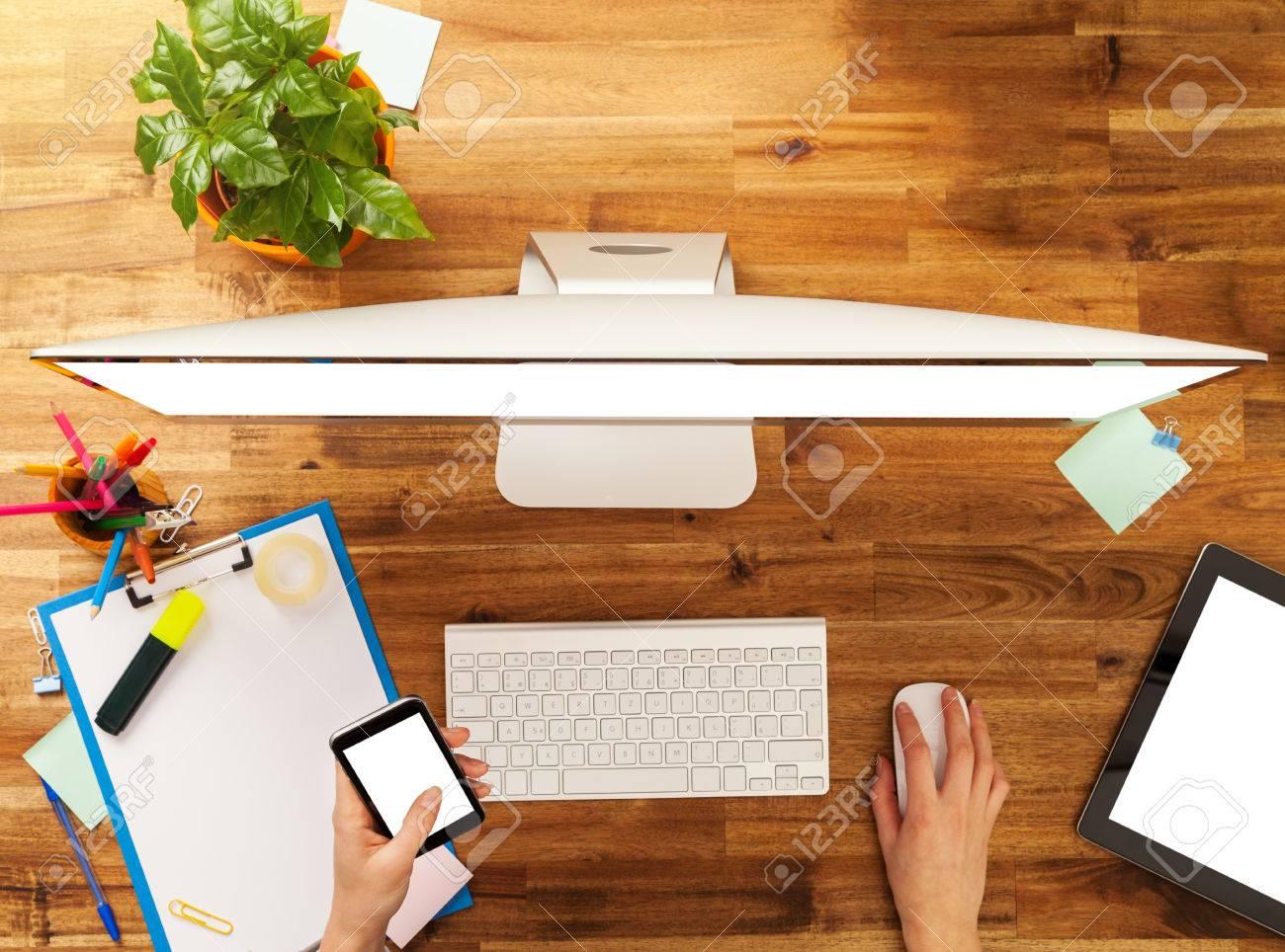 Femme au travail avec un ordinateur placé sur le bureau en bois