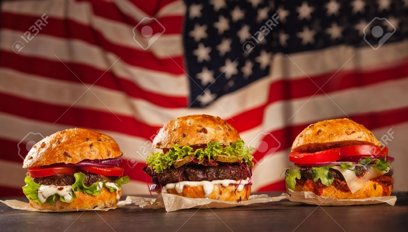 Delicious hamburgers served on wooden planks. Flag of USA as background - 47420827