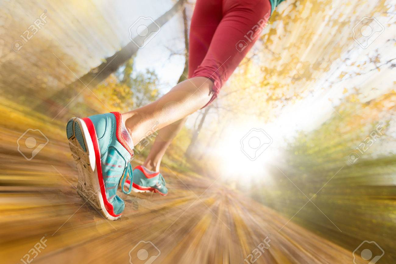 Close up of feet of female runner running in autumn leaves. Fitness exercise. Blur motion - 48032039