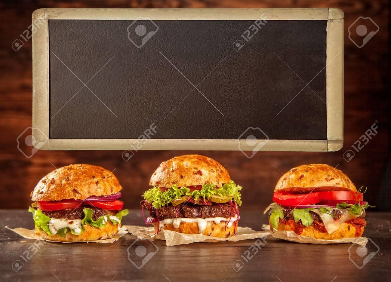 Délicieux hamburgers faits maison avec tableau noir servi sur un