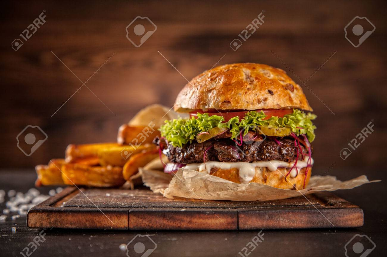 Delicious home made hamburger with lettuce and cheese, served on wooden desk - 50529468