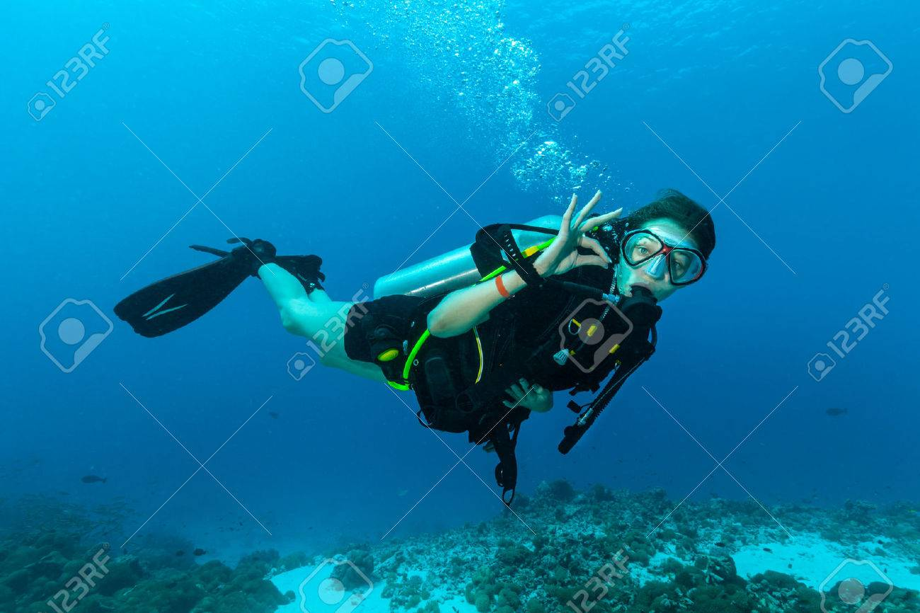 Young female scuba diver underwater showing ok signal - 52507572