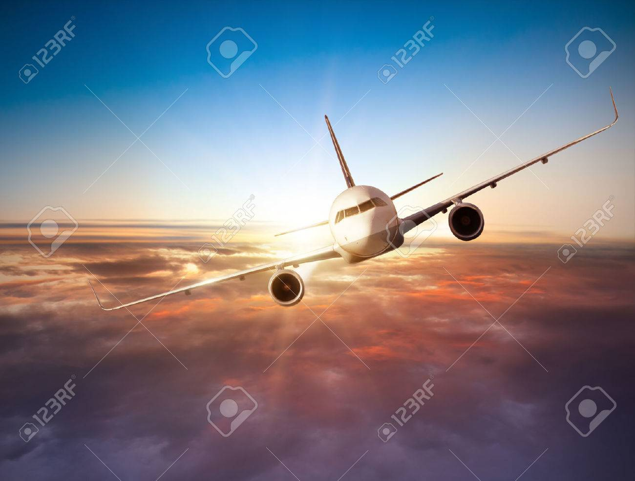 Commercial airplane flying above clouds in dramatic sunset light - 54624094