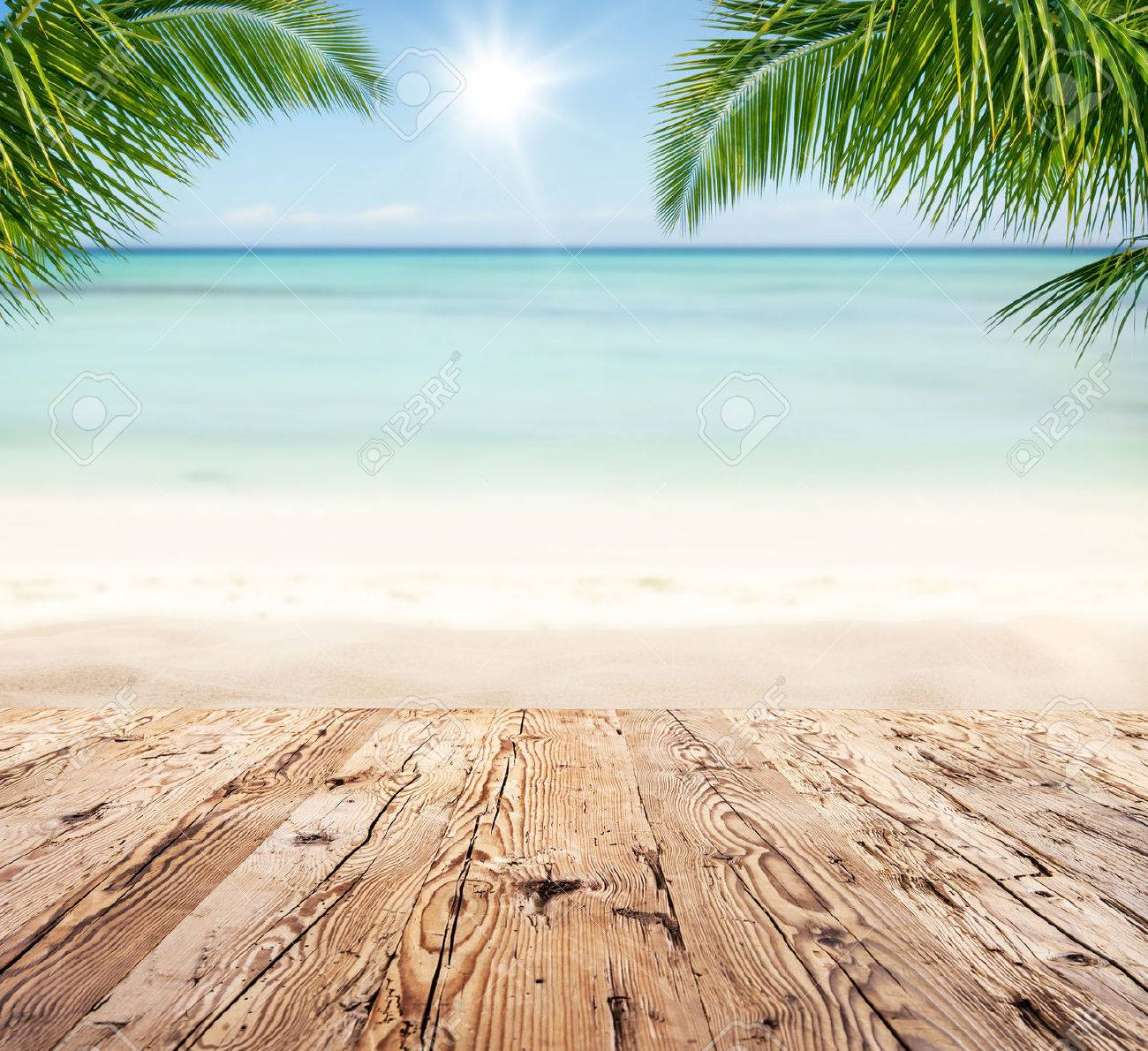 Empty wooden planks with blur beach on background, can be used for product placement, Palm leaves on foreground - 55296508