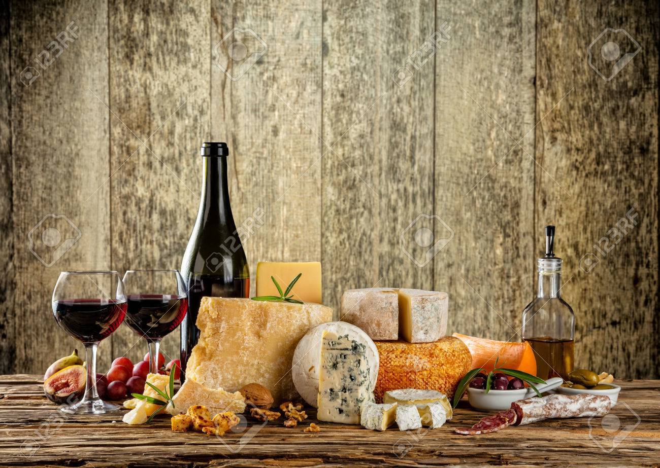 Various types of cheese, glasses and bottle of red wine placed on wooden table, copyspace for text. Wooden planks on background - 57547654