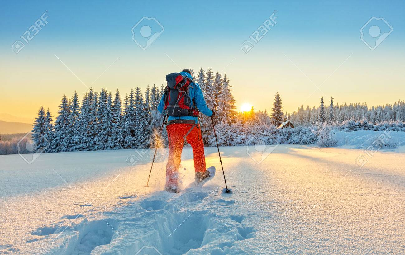 Snowshoe walker running in powder snow with beautiful sunrise light. Outdoor winter activity and healthy lifestyle - 69285930