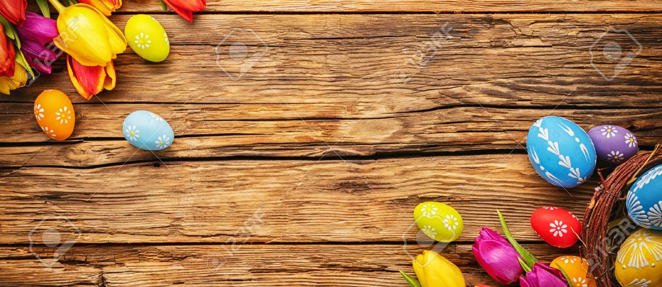 Easter eggs with tulips on wooden board, easter holiday concept. Copyspace for text. - 70485346