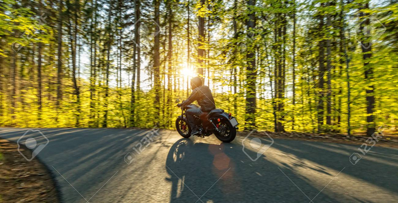 Motorcycle driver driving in forest, beautiful sunset - 70587276