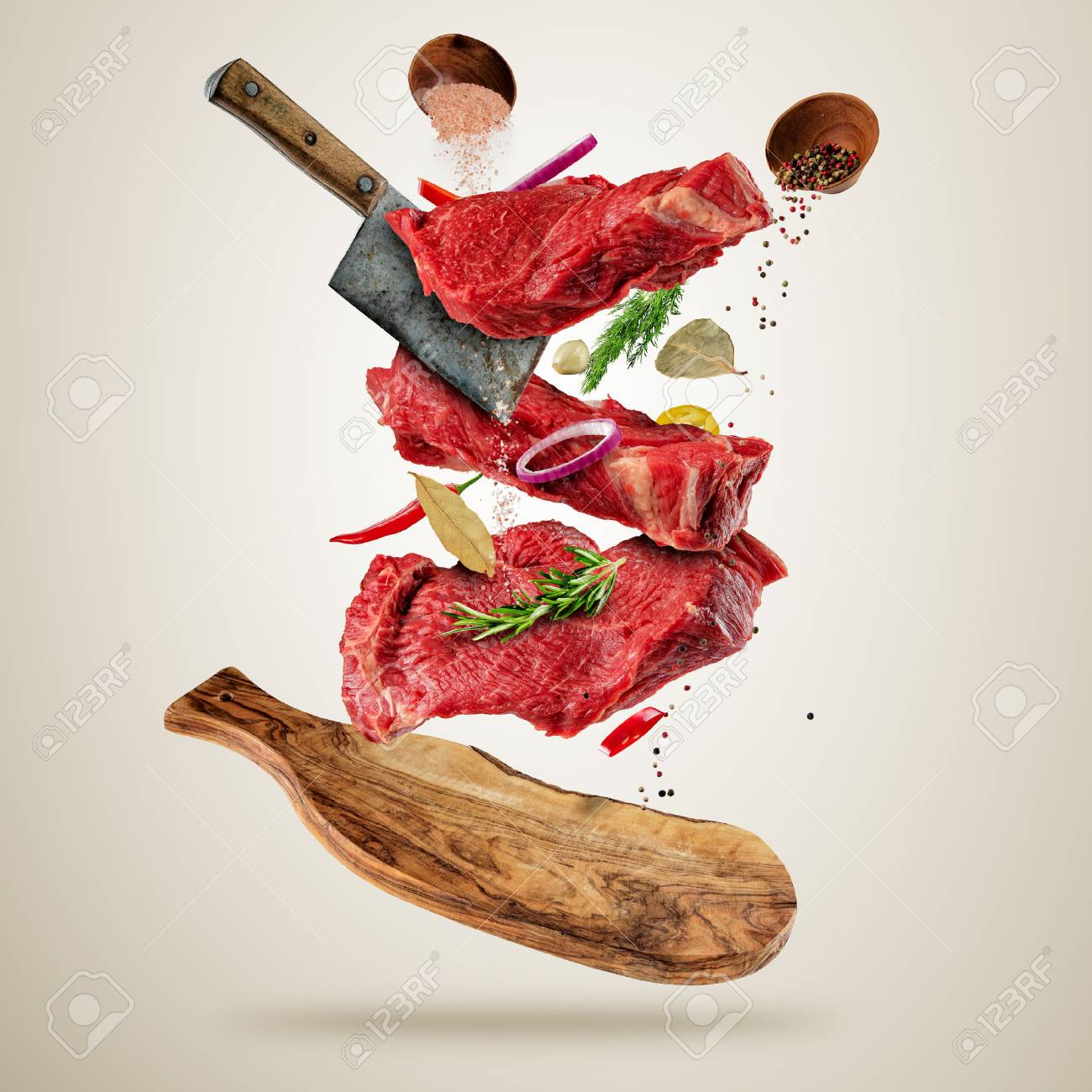 Flying pieces of raw beef steaks, with herbs, served on woodenboard. Meat chopper cuting the flesh. Concept of food preparation in low gravity mode. Separated on smooth gray background - 74520641