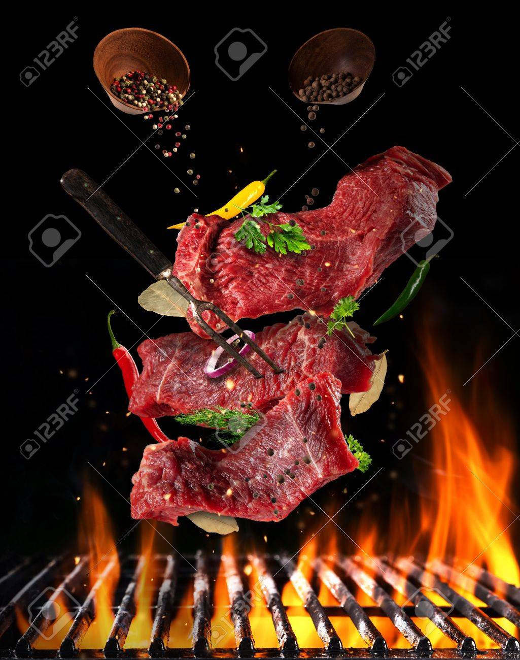 Flying pieces of raw steaks, with ingredients for cooking, barbecue grill with fire flames. Concept of food preparation in low gravity mode. Separated on smooth background - 76366202