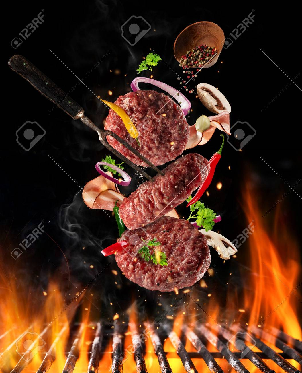 Flying raw milled beef meat, with ingredients for cooking above grill fire. Freeze motion of cooking staff. Fork holding the meat. Concept of food preparation in low gravity mode. - 76366193