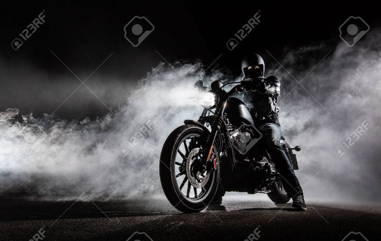 High power motorcycle chopper with man rider at night. Fog with backlights on background. - 78406752