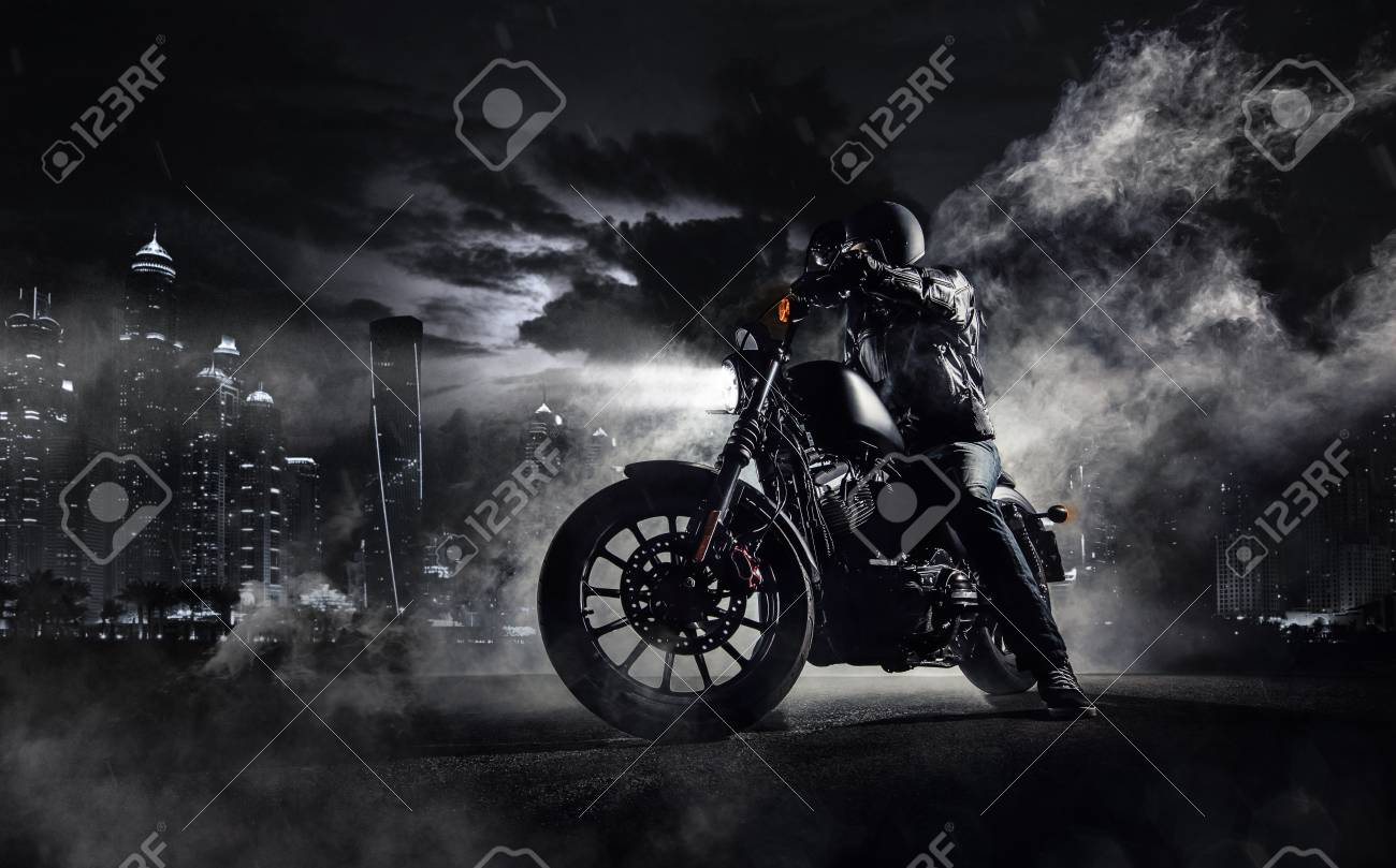 Detail of high power motorcycle chopper with man rider at night. Modern city of Dubai and fog with backlights on background. - 80901327