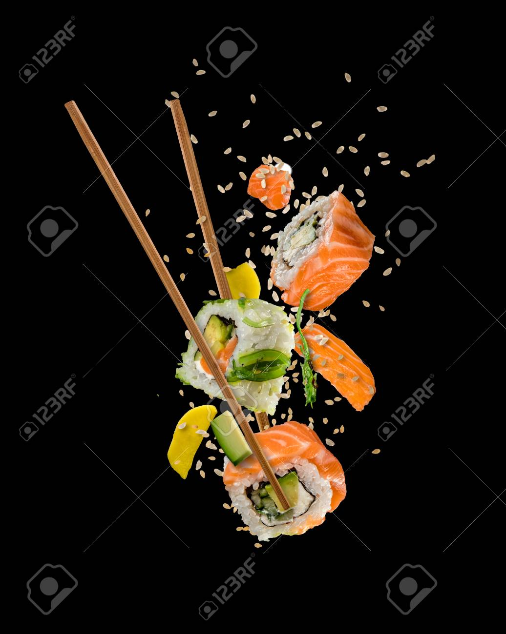 Sushi pieces placed between chopsticks, separated on black background. Popular sushi food. - 80901332