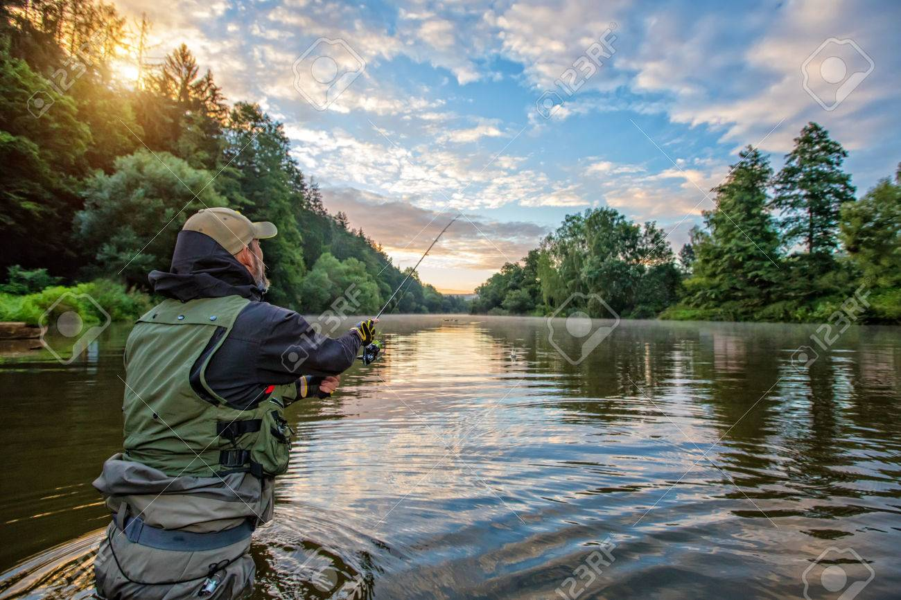 Sport fisherman hunting predator fish. Outdoor fishing in river during sunrise. Hunting and hobby sport. - 83543730