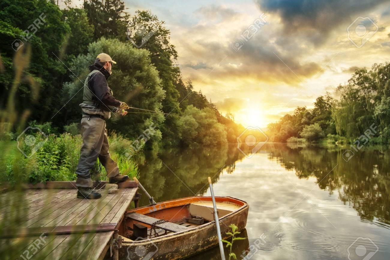 Sport fisherman hunting predator fish from wooden pier. Outdoor fishing in river during sunrise. Hunting and hobby sport. - 83602457