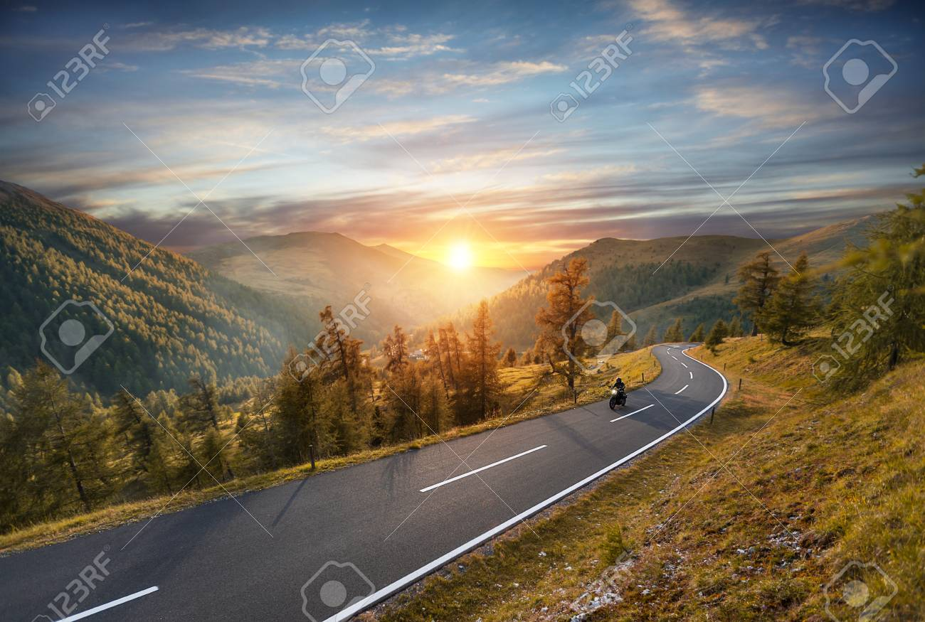 Motorcycle driver riding in Alpine highway, Nockalmstrasse, Austria, Europe. Outdoor photography, mountain landscape. Travel and sport photography. Speed and freedom concept - 84981825