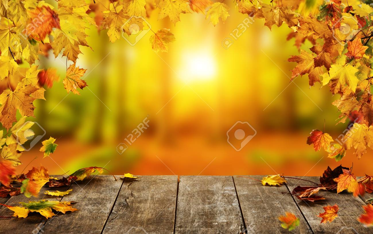 Autumn background with falling leaves and empty wooden table, ideal for product placement or free space for text. Seasonal abstract vivid colored background - 90021868
