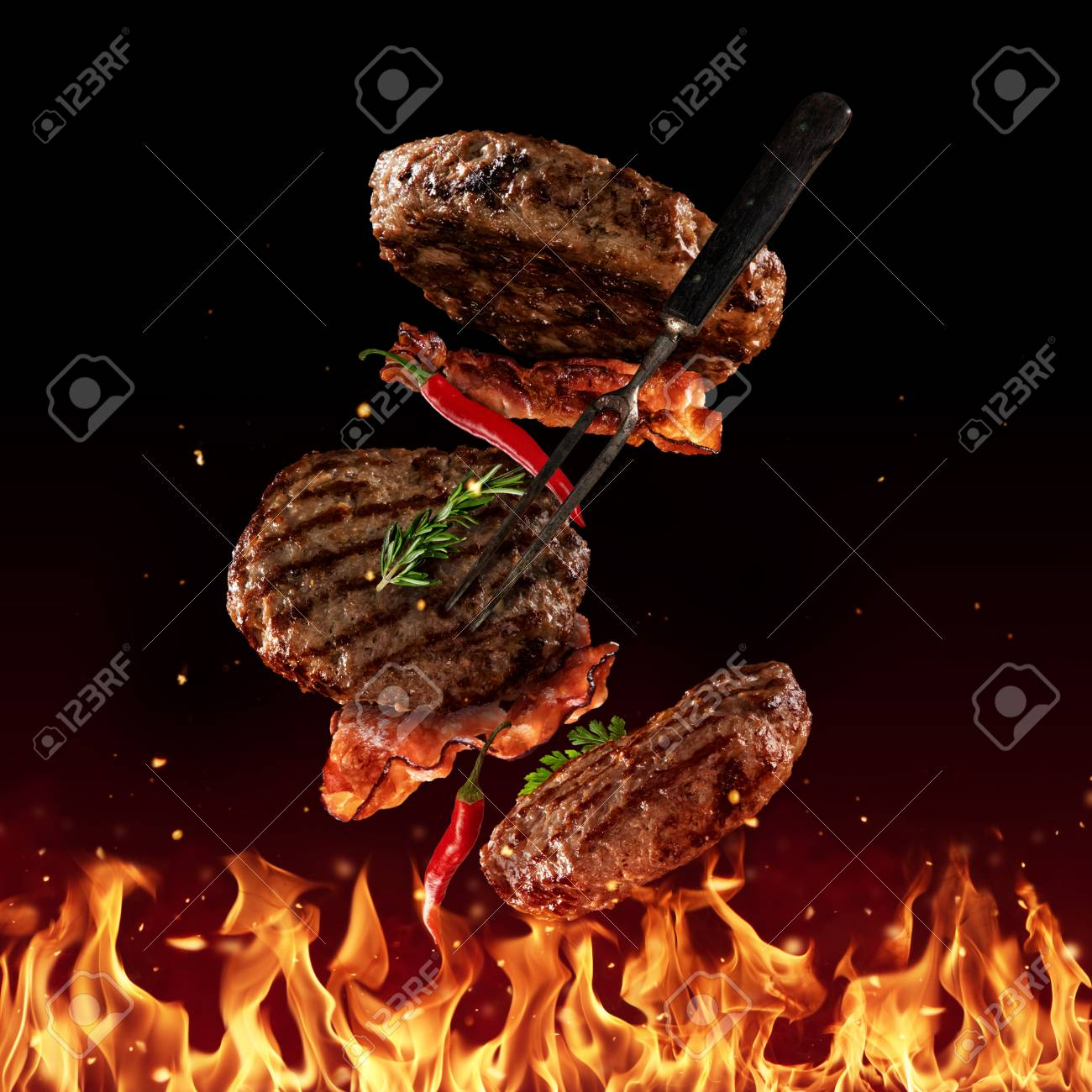 Flying beef minced hamburger pieces above grill flames, isolated on black background. Concept of flying food, very high resolution image - 101648294