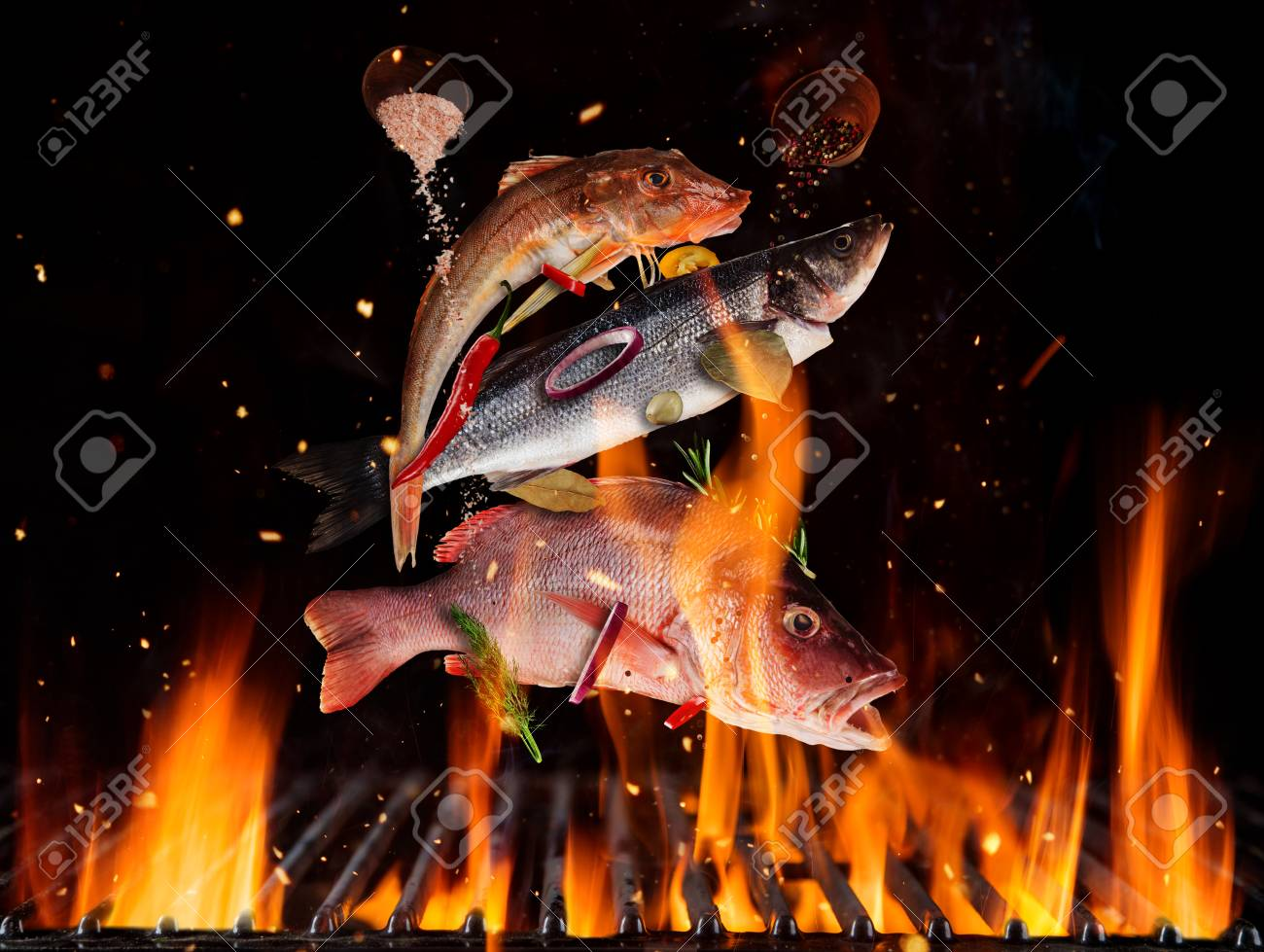 Flying sea fish above burning grill grid, isolated on black backround. Barbecue and grill concept - 120029773