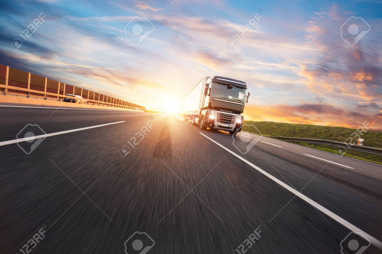 European truck vehicle on motorway with dramatic sunset light. Cargo transportation and supply theme. - 128510286