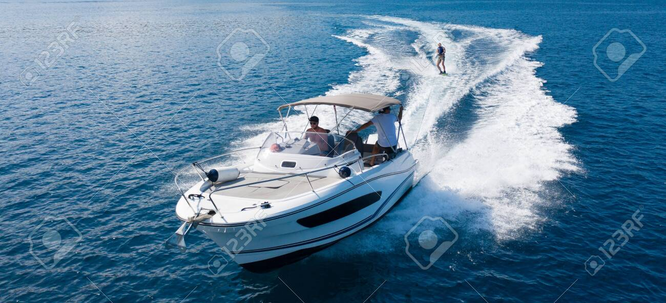 Speedboat with wakeboard rider on open sea. Leasure activities and adrenalin sport concept - 130340227