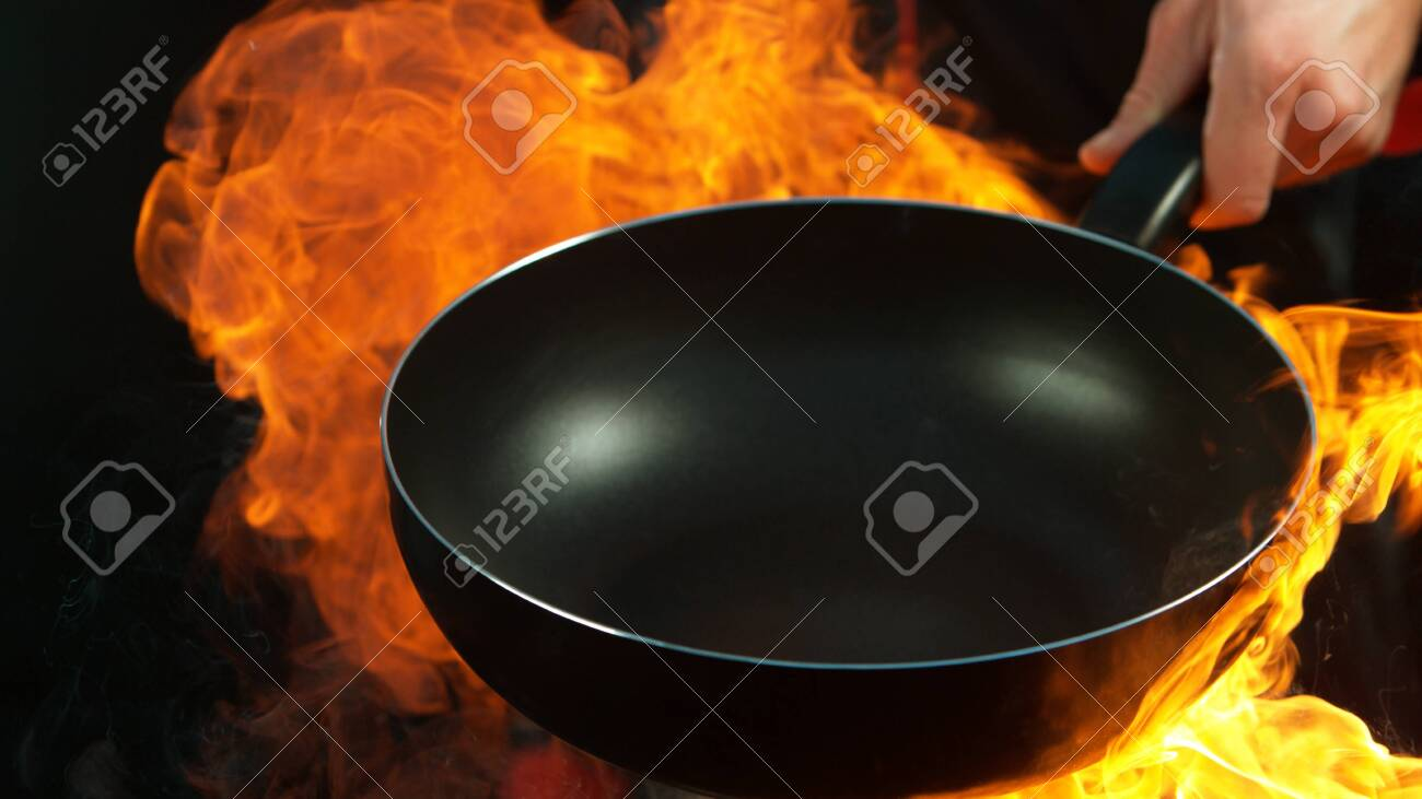 Closeup of chef holding empty wok pan with flames. Isolated on black background - 131513238
