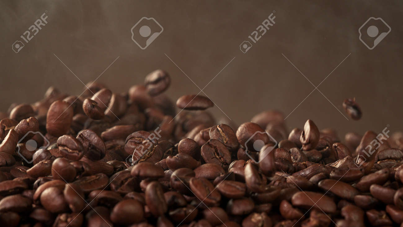 Pile of roasted cocoa beans, whole unpeeled pieces, free space for text. - 168111157