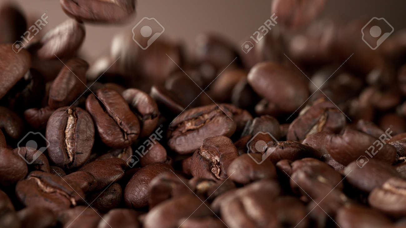 Pile of fresh roasted coffee beans with smoke around. Delicious coffee background - 168093356
