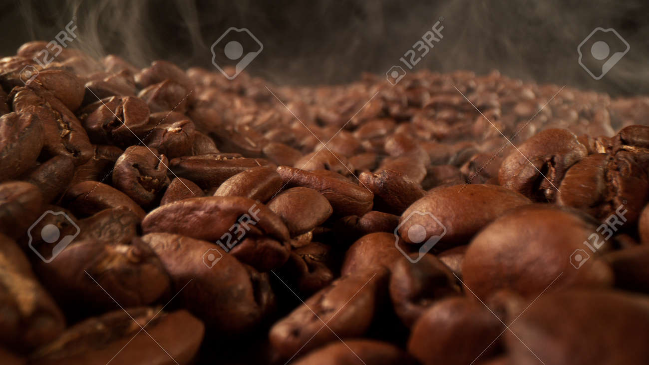 Pile of fresh roasted coffee beans with smoke around. Delicious coffee background - 168093359