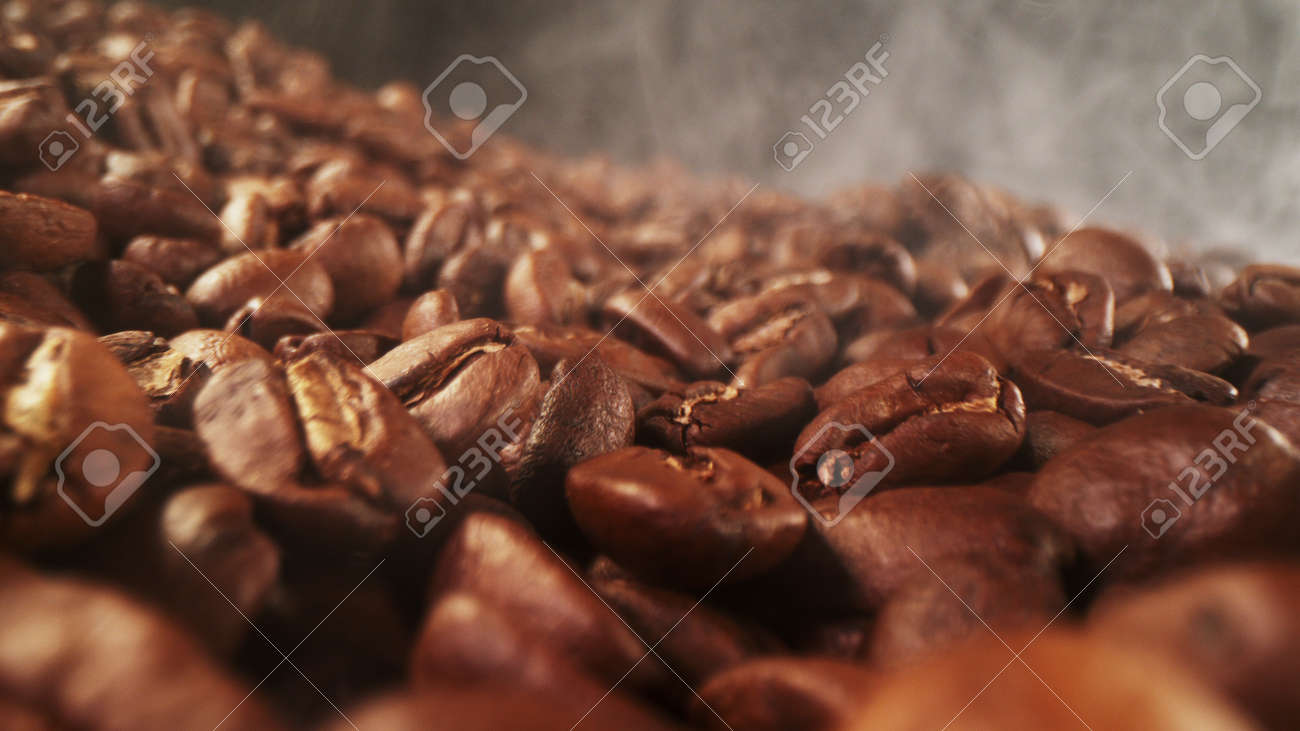 Pile of fresh roasted coffee beans with smoke around. Delicious coffee background - 168093358