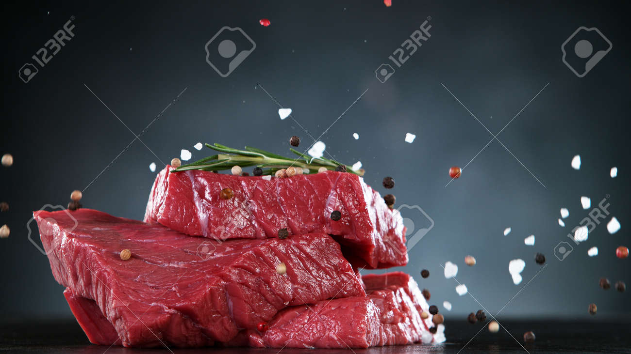 Raw beef steaks on stone table, ready to cook. Free space for text. - 168510294