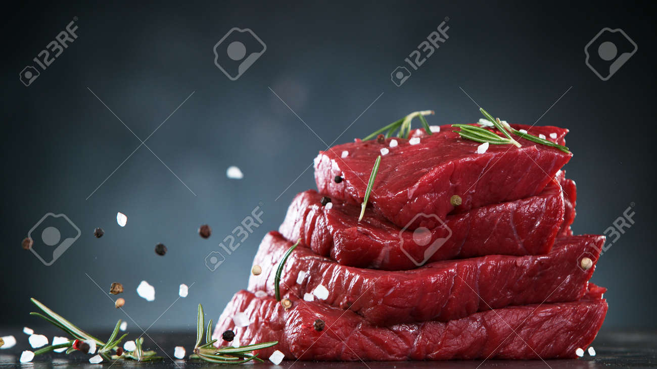 Raw beef steaks on stone table, ready to cook. Free space for text. - 168510295