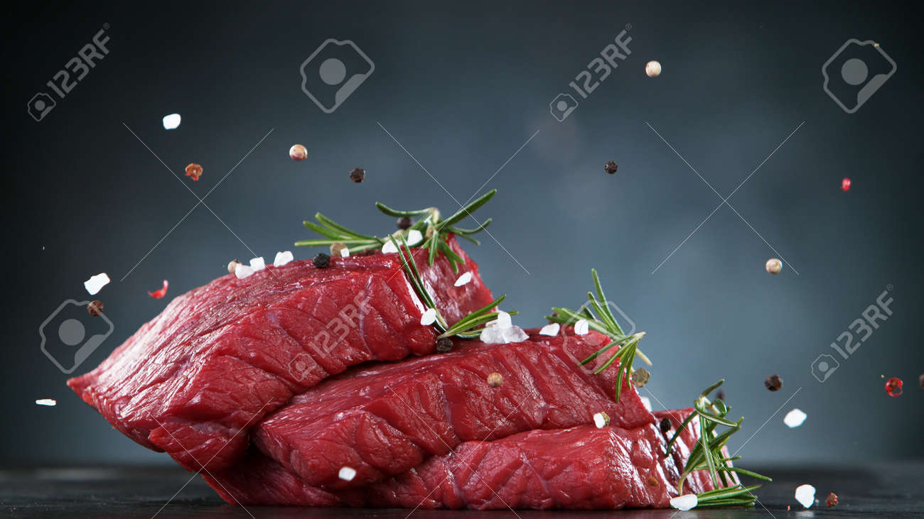 Raw beef steaks on stone table, ready to cook. Free space for text. - 168510296