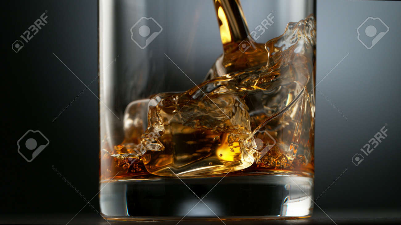 Pouring Glass of scotch whiskey and ice. Freeze motion of splashing liquid. - 170236871