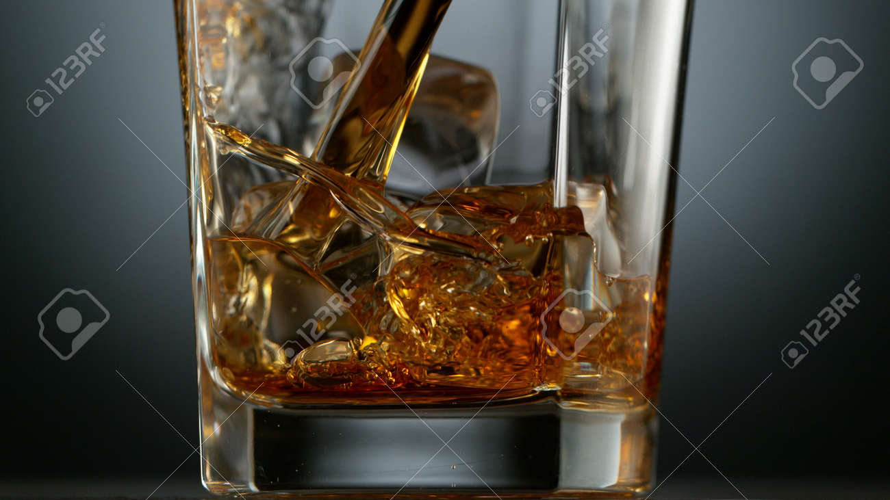 Pouring Glass of scotch whiskey and ice. Freeze motion of splashing liquid. - 170236873