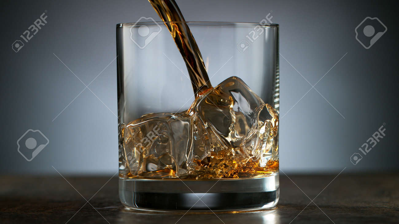 Pouring Glass of scotch whiskey and ice. Freeze motion of splashing liquid. - 170236973