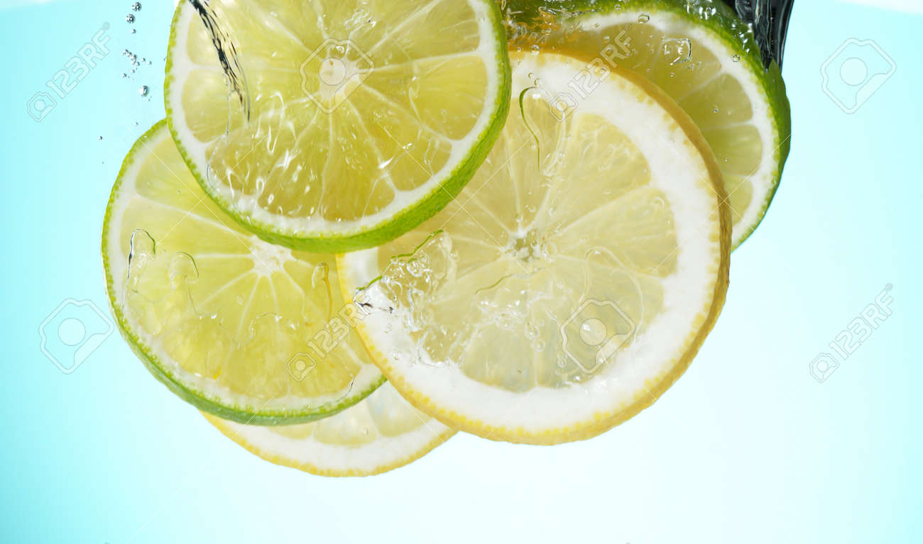 Fresh lime dropped into water with splash and ice cubes. Studio shot with clear background. - 170440652